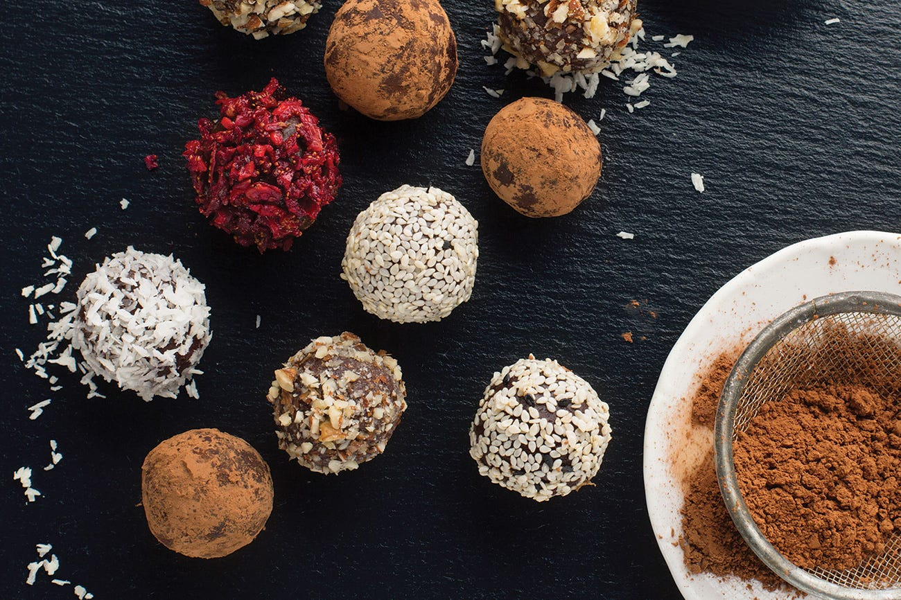 A variety of chocolate truffles and a bowl of cocoa powder